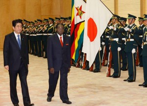 President Robert Mugabe walks with Prime Minister Shinzo Abe as they review an honour guard before their meeting at Abe's office Monday