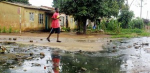 A man crosses a street flooded by sewage in the township of Dzivaresekwa in Harare