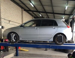 A vehicle undergoing a wheel alignment service