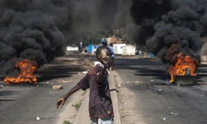 A protester throws rocks next to burning tyres during a demonstration against President Robert Mugabe. Photograph: STRINGER/AFP/Getty Images