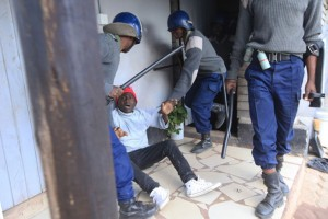 Armed Zimbabwean police detain an alleged rioter in Harare, Monday, July, 4, 2016, as police in the capital fired tear gas and water cannons to quell rioting by taxi and mini bus drivers.  The violence came amid a surge in protests in recent weeks because of economic hardships and alleged mismanagement by the government of President Robert Mugabe. (AP Photo/Tsvangirayi Mukwazhi)